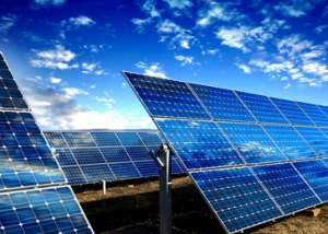 Rows of photovoltaic solar panels and blue sky with clouds